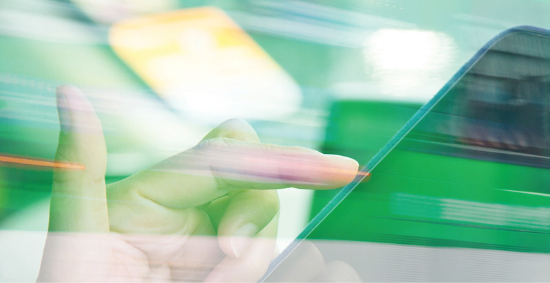 Närbild på hand som pekar på en telefon, grönt filter över bilden.