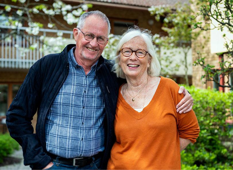 En man och kvinna i 60-årsåldern som glada tittar in i kameran och håller om varandra. I bakgrunden syns en lummig innergård.
