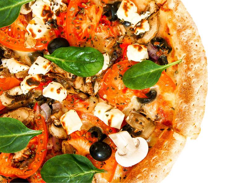 Ett utsnitt på en gräddad pizza med fetaost och spenat.
